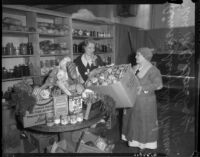 Aimee Semple McPherson and Mrs. M. B. Godbey in a pantry preparing food baskets, Los Angeles, 1935