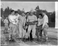 Football players gathered around the playbook during practice, Los Angeles
