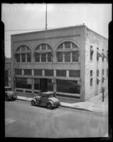 "Two vehicles parked in front of the old ""Post-Record"" building, Los Angeles, 1930s"