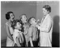 Nora Olsen, school nurse, inspecting students, Los Angeles, 1936