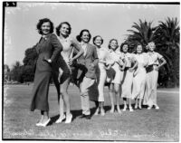 Line of actresses and models standing with their hands on their hips in a grassy field, Los Angeles, 1936