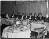Prominent figures in the motion picture industry seated together at a banquet table, Los Angeles, 1930s