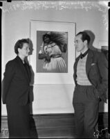 John Coleman Burroughs, standing next to his wife J.C. Coleman, exhibits oil paintings at Stendahl Gallery, Los Angeles, 1937