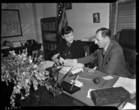 Film actress Anna May Wong looking over an extortion letter with District Attorney Buron Fitts, Los Angeles, 1937