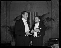 Actors Paul Muni and Victor McLaglen holding an Oscar at the Academy Awards, Los Angeles, 1937