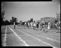 Track athletes pass batons in a relay event during the All-City High School track and field meet, Los Angeles, 1937