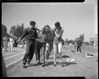 Track athletes support an injured teammate, Los Angeles, 1937