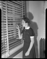 Cult victim Delight Jewett peering through blinds in U.S. Attorney Fleet Palmer's office, Los Angeles, 1937