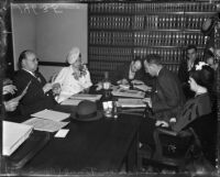 Evangelist Aimee Semple McPherson conferring with her attorneys over paperwork, Los Angeles, 1937