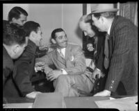Film actor Clark Gable sitting with a group of admirers, Los Angeles, 1937