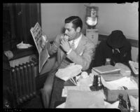 Film actor Clark Gable eating a sandwich and reading a newspaper in an office, Los Angeles, 1937