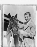Film actor Clark Gable with his horse Beverly Hills on his ranch, Los Angeles, 1937