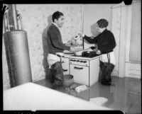 Mr. and Mrs. Frank Foster wearing waders in their flooded kitchen, Long Beach, 1937