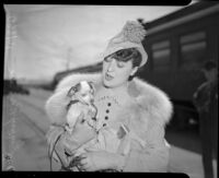 Burlesque dancer Gypsy Rose Lee holds her small dog by a train, Los Angeles, 1930s