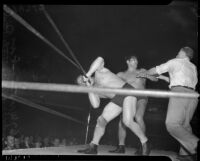 Referee getting between wrestlers Gus Sonnenberg and Baptiste Paul's battle at the Olympic, Los Angeles, 1937