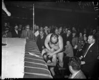 Wrestlers Bluebeard Lewis and Baron Benny Ginsberg grapple outside the ring, May 26, 1937
