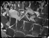 Wrestlers Vincent López and Gino Garibaldi take their fight into the stands at Olympic Auditorium, Los Angeles, 1937