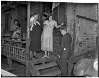 Poverty-stricken family speaks to unidentified man outside of their dilapidated home, Los Angeles, 1930s