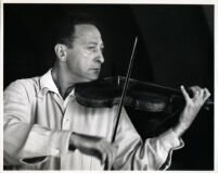 Jascha Heifetz playing the violin, 1957 [descriptive]
