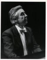 Walter Klien playing the piano in concert attire, 1986 [descriptive]