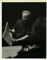 Sir Charles Mackerras consulting a score during rehearsal, 1986 [descriptive]