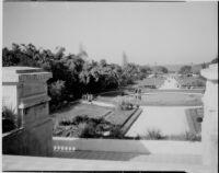 View from a terrace at the Jardin d'Essais towards a pool and people on a long promenade, Algiers, 1929