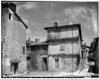 Three story building in a community of closely built buildings and narrow streets, Maisse, France, 1929