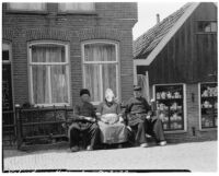 Woman and two men in traditional Dutch clothing sitting in front of a brick building, Volendam, Netherlands, 1929