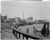 Man leans against a docked boat on the waterfront in Holland, 1929