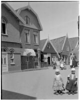Two little girls wearing traditional Dutch clothing outside a row of buildings in Holland, 1929