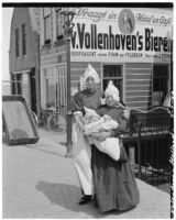 Woman and girl holding a baby in front of a hotel cafe, Volendam, Netherlands, 1929
