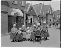 Group of seven little girls in traditional Dutch clothing on a shopping street, Holland, 1929
