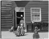 Three little girls and a woman wearing traditional Dutch clothing outside a house, Holland, 1929