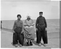 Woman and two men in traditional Dutch clothing standing in front of the ocean, Holland, 1929
