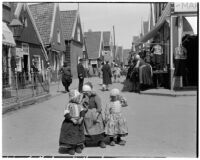 Three little girls wearing traditional Dutch clothing with a crowd of shoppers in the background, Holland, 1929