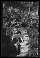Rosita Dee Cornell standing by a rock wall in a garden, California, 1933