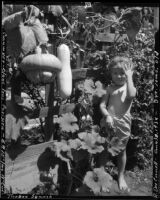 Three-year-old Rosita Dee Cornell standing next to a trellis with cucumber and squash growing on it, California, 1934