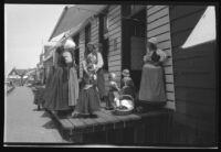 Women and young girls in traditional clothing gathered on a store porch talking, Europe, late 1920s