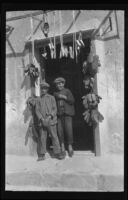 Two young boys standing in a doorway surrounded by hanging bundles of shoes, Europe, late 1920s