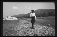 Man standing on a long pile of rocks in a field, Europe, late 1920s