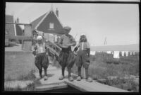 Three children standing on a wooden boardwalk in traditional Dutch clothing, Europe, late 1920s