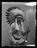 Young man in Indian regalia with trumpet, 1928