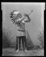 Young man in Indian regalia playing trumpet, 1928