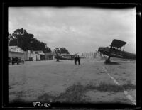 Biplane and men at airfield, [1920s?]