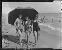 Young women posing on beach with umbrella and seaweed, Pacific Palisades, 1927