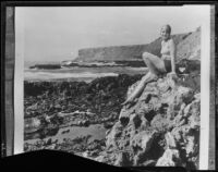 Young woman posing on rocks overlooking beach, Malibu, 1929
