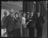 Women pinning boutonnieres on men, 1936