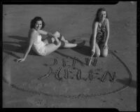 Young women writing in sand, Santa Monica, 1938