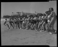 Young people posing for tug-of-war game on beach, Santa Monica, 1938