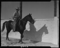 Cowboy riding horse on dirt road next to affluent residential property, Palm Springs